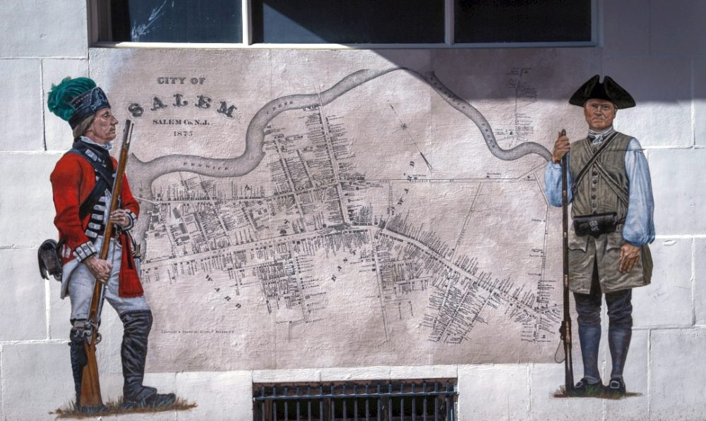 Illustration of map of Salem City with two men with muskets next to it